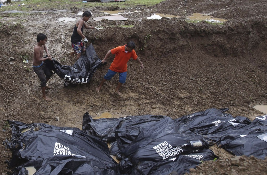 Filipino workers bring body bags to a mass burial site at Baspe public cemetery at typhoon-hit Tacloban, Leyte province, central Philippines on Thursday. Typhoon Haiyan, one of the most powerful storms on record, hit the country's eastern seaboard last Friday, destroying tens of thousands of buildings and displacing hundreds of thousands of people.