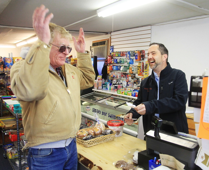 Matt Williams, right, owner of Andy's Handy Store in Yarmouth, has fun with customer Ronnie Thoits Saturday. Residents want postal services restored in the shop.