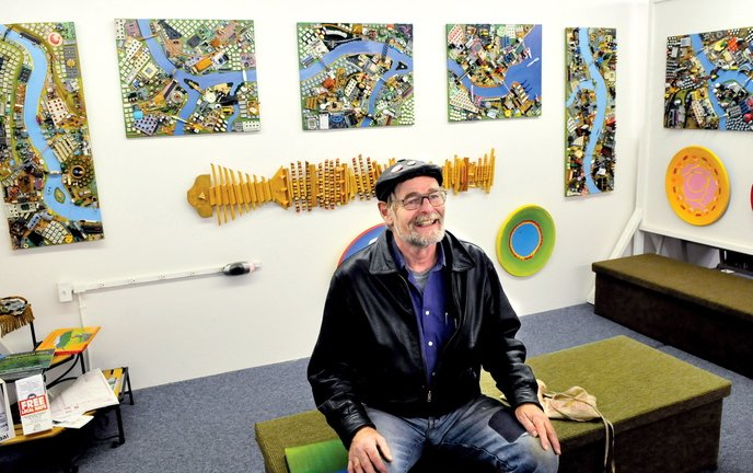 """Artist Wally Warren speaks about his art including """"City of Dreams,"""" which is exhibited behind him at the Central Maine Artists Gallery in Skowhegan on Thursday."""