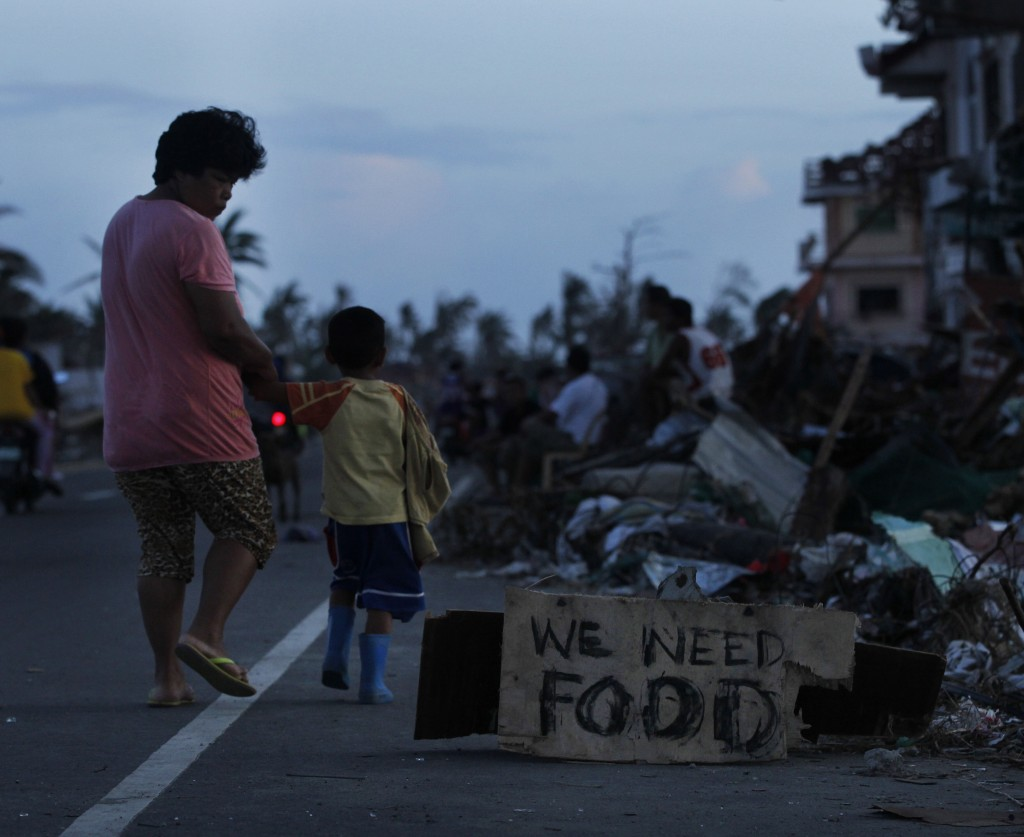 A mother walks with her son past a plea for food on Friday in a neighborhood decimated by Typhoon Haiyan in Tacloban, Philippines. The death toll is estimated at 3,600 to 4,460.