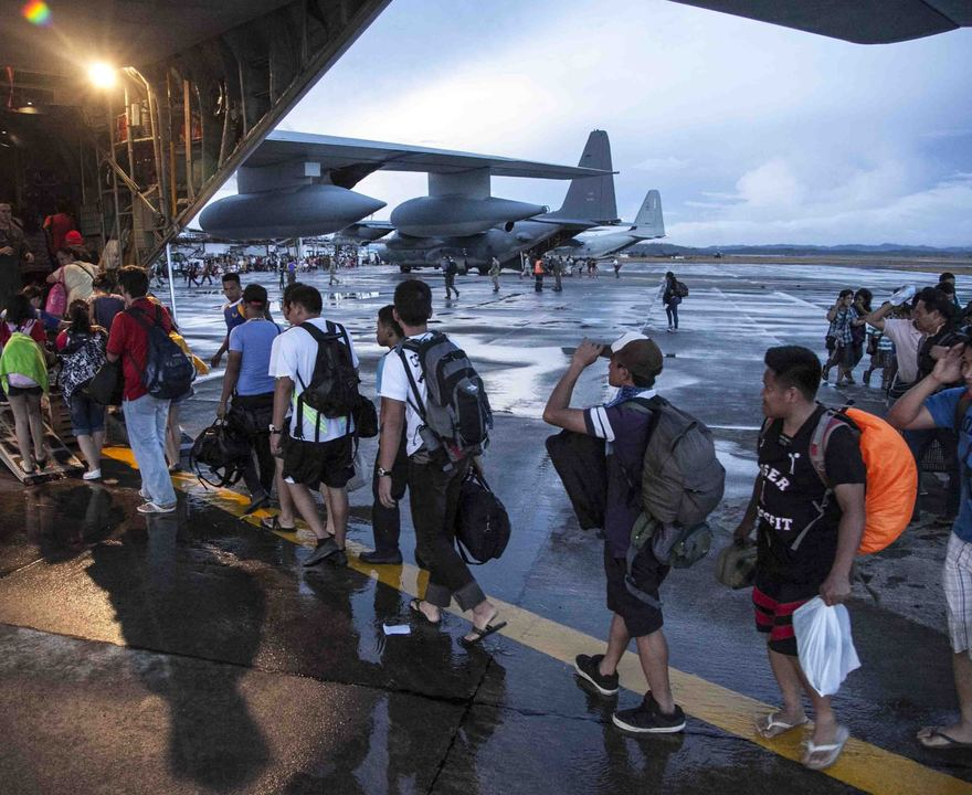 Civilians displaced by Typhoon Haiyan board a U.S. Marine Corps transport plane at Tacloban Air Base in Tacloban, Philippines, before being flown to Manila on Wednesday.
