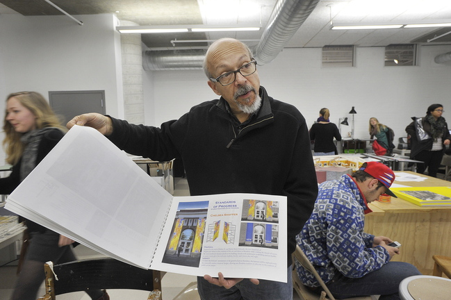 Art department faculty member Mark Wethli shows examples of the work of students in his public art class.