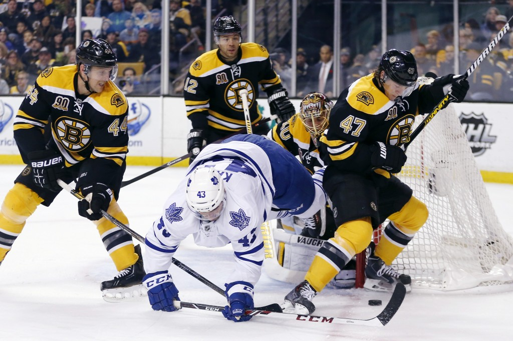 Toronto Maple Leafs' Nazem Kadri (43) falls while battling Boston Bruins' Torey Krug (47) and Dennis Seidenberg (44), of Germany, for the puck in the first period of an NHL hockey game in Boston, Saturday, Nov. 9, 2013.