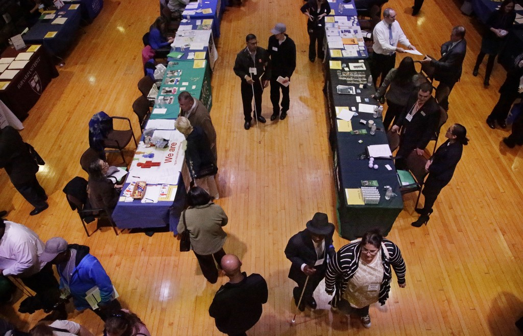 Job seekers and their volunteer guides attend a job fair for the visually impaired in the former Radcliffe College gymnasium, at Radcliffe Yard in Cambridge, Mass., last month. Helen Keller exercised here en route to becoming the first deaf/blind person to earn a bachelor of arts degree in 1904.