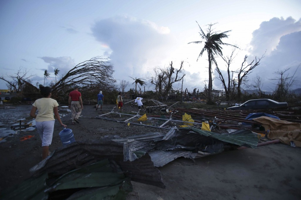 "Residents walk by debris after powerful Typhoon Haiyan slammed into Tacloban city, Leyte province, central Philippines on Saturday, Nov. 9, 2013. The central Philippine city of Tacloban was in ruins Saturday, a day after being ravaged by one of the strongest typhoons on record, as horrified residents spoke of storm surges as high as trees and authorities said they were expecting a ""very high number of fatalities."""