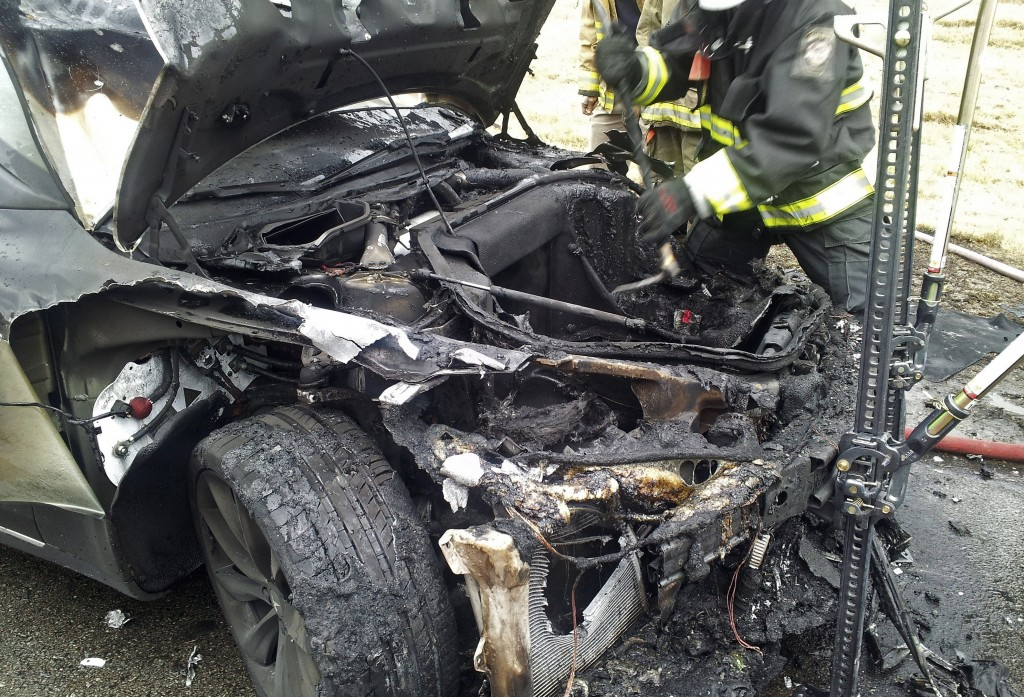 Emergency workers respond to a fire on a Tesla Model S electric car in Smyrna, Tenn. This car and another in Washington state are the subject of an investigation because they caught fire after running over debris in the road.