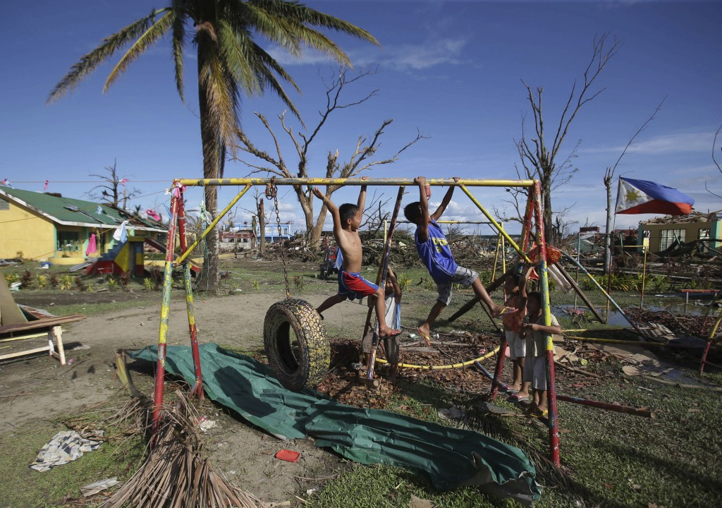 Children play on the playground of the typhoon damaged Pawing Elementary School in Palo town, Leyte province, central Philippines Tuesday, Nov. 19, 2013. Hundreds of thousands of people were displaced by Typhoon Haiyan, which tore across several islands in the eastern Philippines on Nov. 8.