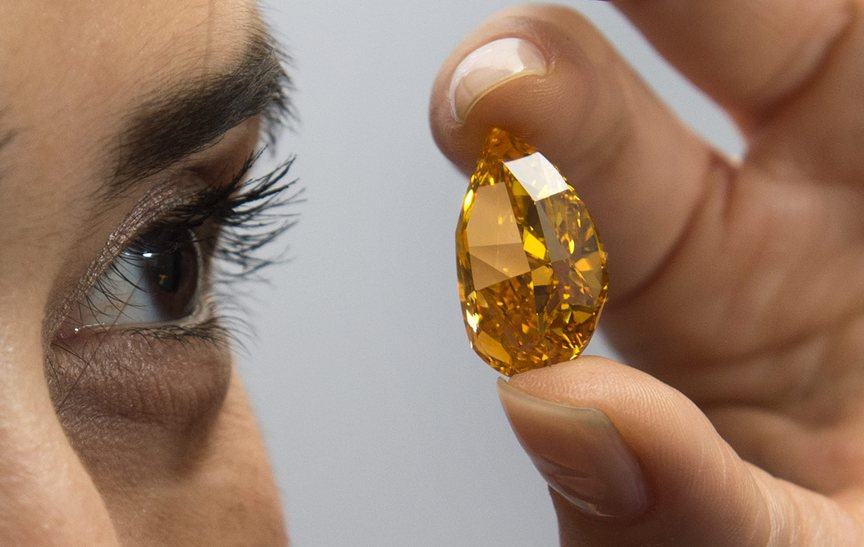 A Christie's employee displays the 14.82-carat pear-shaped orange diamond that was auctioned off Tuesday in Geneva.