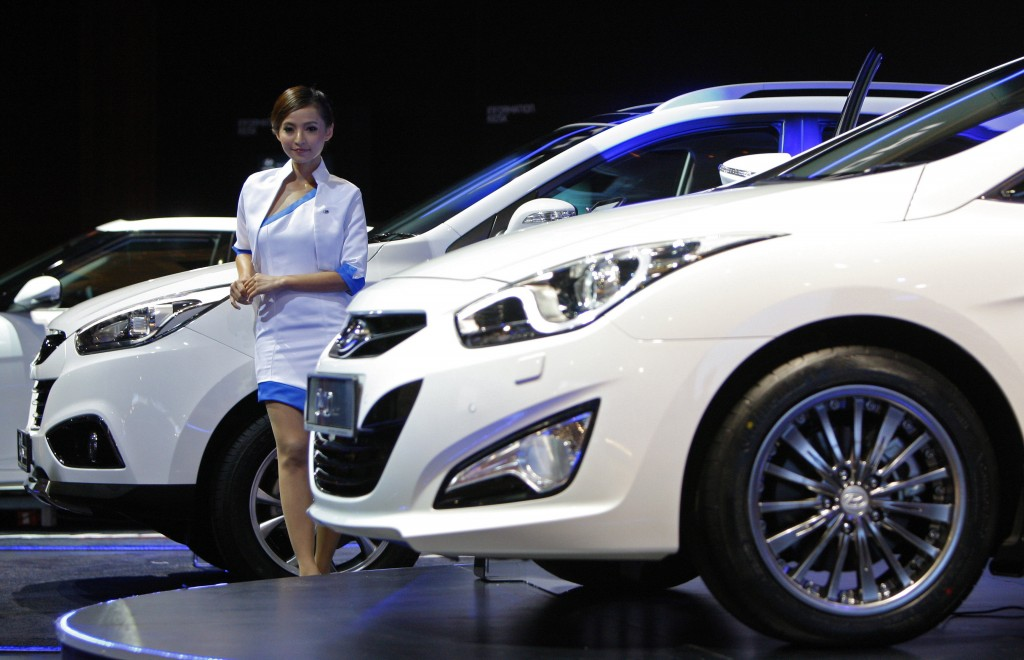 A model poses next to a Hyundai Tucson on display at the Kuala Lumpur International Motor Show in Malaysia.