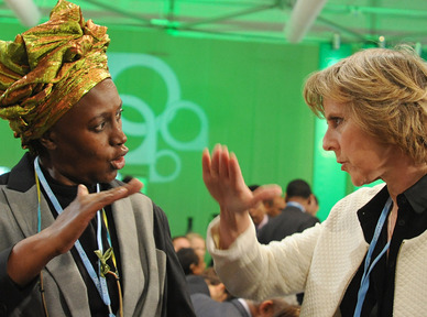 """Alice Akinyi Kaudia of Kenya, left, talks with European Climate Commissioner Connie Hedegaard at the U.N. climate change conference in Warsaw, Poland, last week. Hedegaard said Sunday that the international conference ought to provide a """"substantial answer"""" to global warming by 2015."""