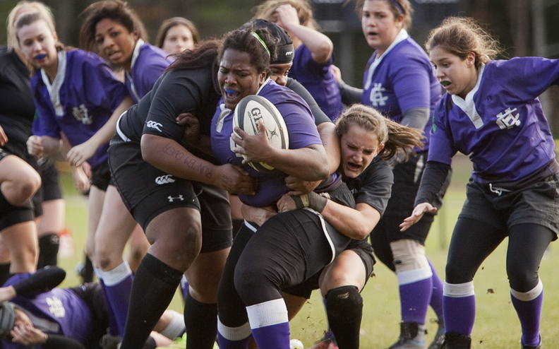 Bowdoin College women's rugby players Pamela Zabala, left, holding onto the ball carrier, and Addison Carvajal try to tackle a Holy Cross player during a playoff game in Brunswick on Saturday. Bowdoin plays in the national quarterfinals this Saturday.