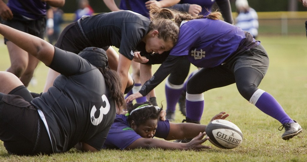 Bowdoin College women's rugby team member Addison Carvajal puts her head into a Holy Cross player as her teammate passes the ball during playoff action in Brunswick last Saturday.