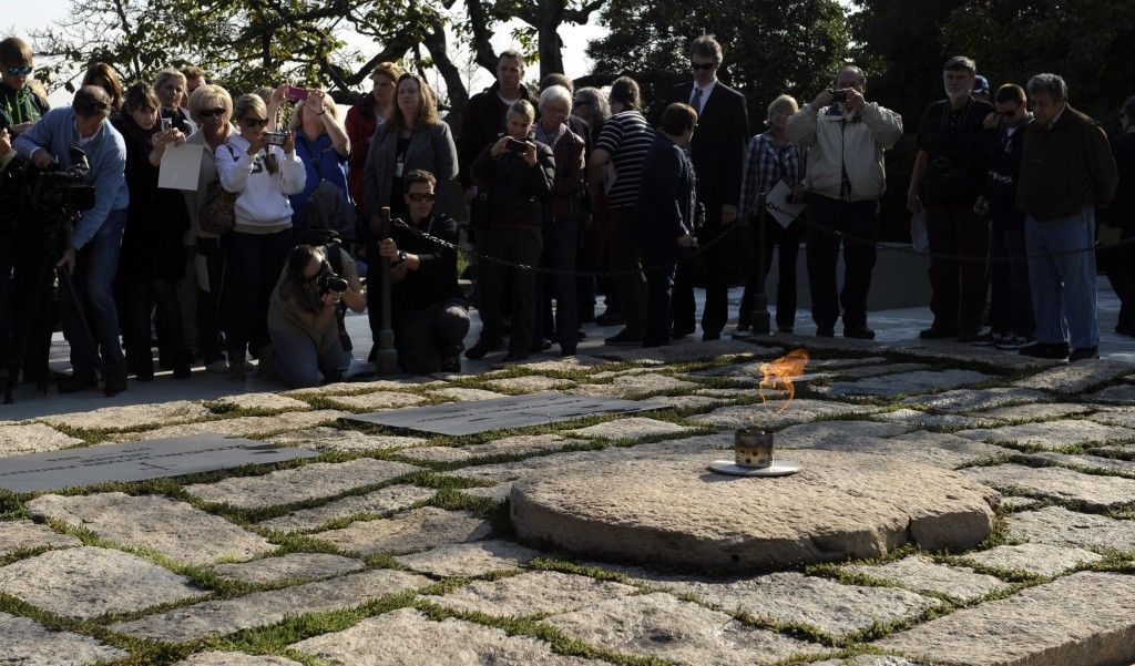 People visit the eternal flame at the gravesite of former President John F. Kennedy as it burns at Arlington National Cemetery in Arlington, Va. President Barack Obama will visit the gravesite of John F. Kennedy and pay tribute to two signature initiatives begun by the slain president as the nation observes the 50th anniversary of his assassination in the coming week.