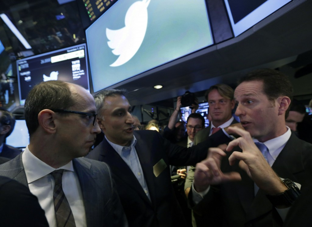 Twitter CEO Dick Costolo, left, and Mike Gupta, center, chief financial officer of Twitter, talk with specialist Glenn Carell during Twitter's initial public offering, on the floor of the New York Stock Exchange on Thursday.
