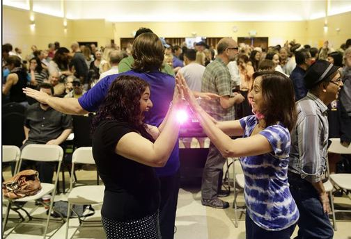 Heina Dadabhoy, left, plays a game with an unidentified attendee at the Sunday Assembly, an athiest congregation founded by British comedians Sanderson Jones and Pippa Evans, on Sunday in Los Angeles.