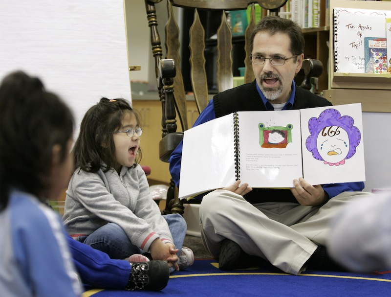 In this March 2007 file photo, Dr. Christopher Lyons, a teacher at Carlin Springs Elementary School, holds a book as he recites to pre-kindergarten students in Arlington, Va. Maine lawmakers were urged Monday to support a bill that would make Maine one of a handful of states to offer pre-kindergarten in every school district.