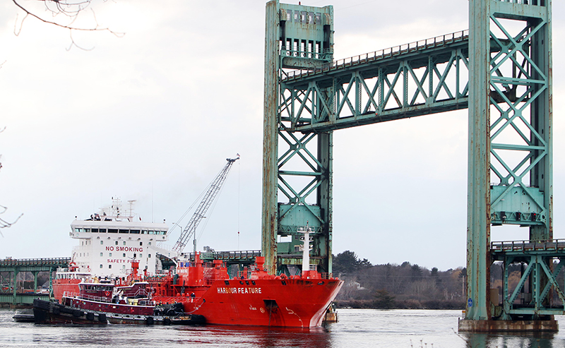 The 473-foot Harbour Feature rests against the Sarah Mildred Long Bridge Monday April 1, 2013 in Portsmouth, N.H. The Coast Guard said the barge somwhow came unattached from the pier and floated free. Following the accident, the tanker was pinned against the bridge with the rising tide of the tidal river.(AP Photo/Jim Cole)