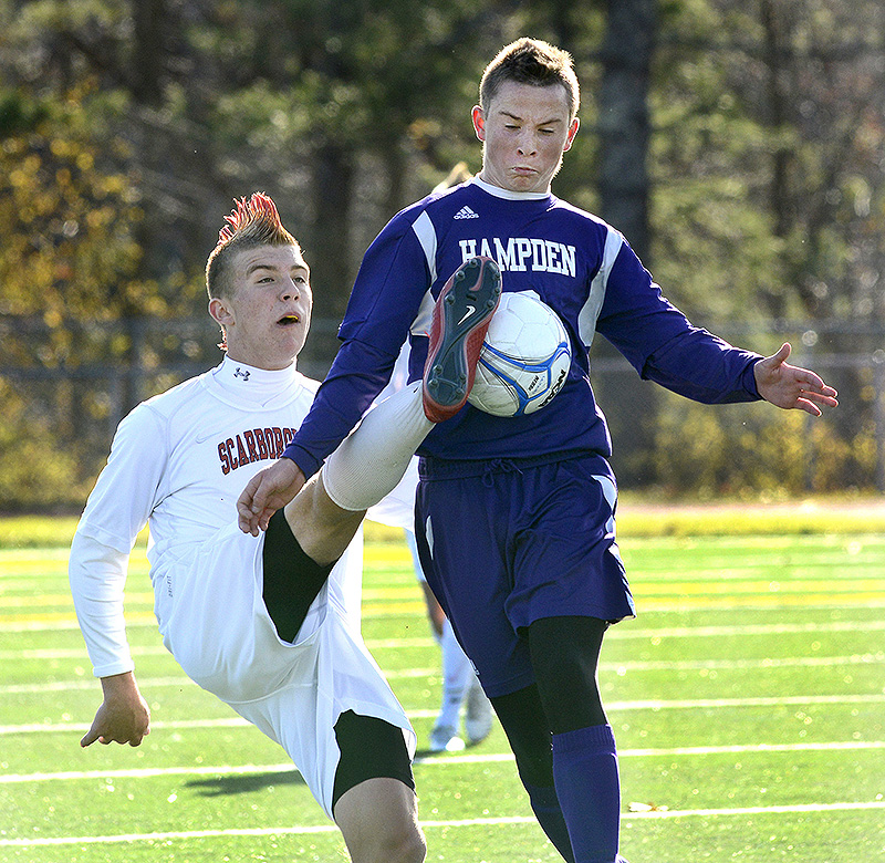 Scarborough's Max Ornstein kicks the ball in front of Hampden Academy's Noah Parker during the Class A state soccer final Saturday. Scarborough won in overtime, 2-1. BoysAsoccer