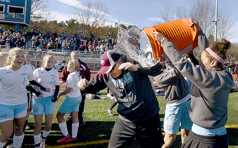 Jeff Fish, Windham's assistant coach, gets doused with a cooler of water after Windham defeated Bangor for the Class A girls' state soccer championship at McMann Field in Bath. GirlsAsoccer