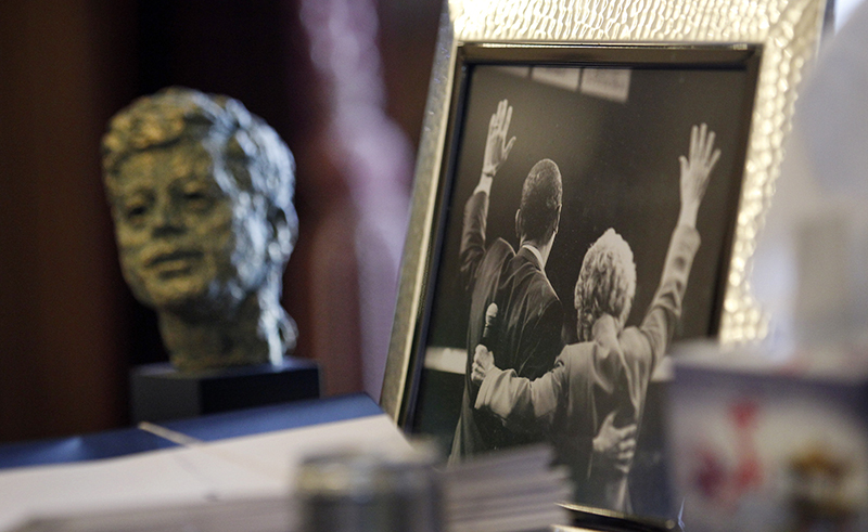 In this Dec. 11, 2012 file photo, a bust of former U.S. President John F. Kennedy sits on the desk of Gov. Chris Gregoire near a photo of Gregoire and U.S. President Barack Obama, in Olympia, Wash. Lisa Pease, a researcher who has studied 1960s assassinations extensively, said at an October 2013 assassination symposium in Pittsburgh,