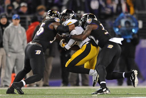 Baltimore Ravens inside linebacker Josh Bynes, left, and strong safety James Ihedigbo tackle Pittsburgh Steelers running back Le'Veon Bell in the first half Thursday in Baltimore.