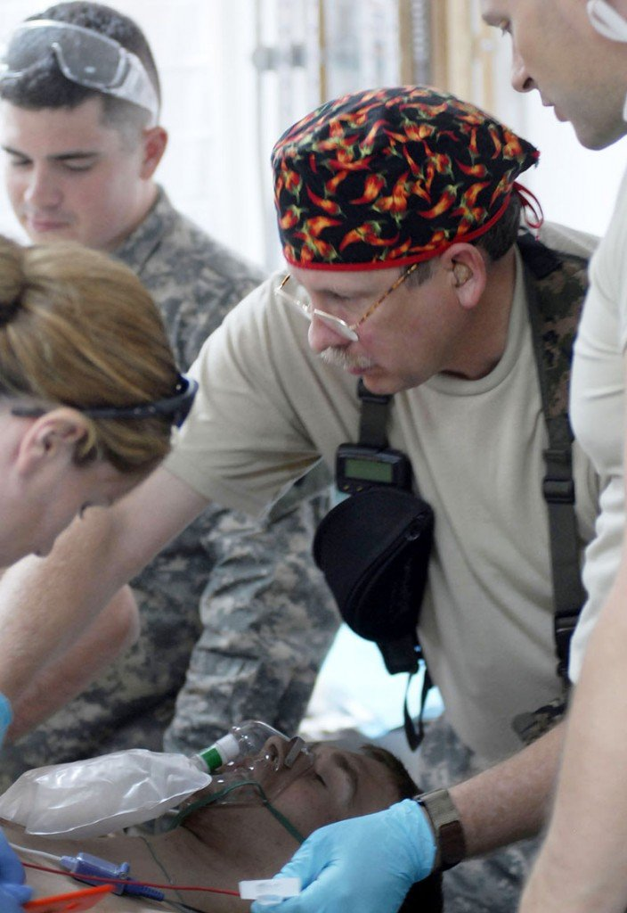 Staff photo/Shawn Patrick Ouellette Lt. Col. Kent Kosmatka of Illinois works with the injured U.S. soldier in the Emergency Medical Treatment Unit at the Army Reserve's 399th Combat Support Hospital in Tikrit, Iraq.