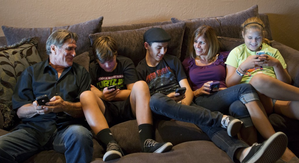 """The Moore family, from left, Bill, Dylan, 13, Randy, 18, Sandra and Alyssa, 12, talk about how they use their smartphones, tablets and computers at their home in San Jose, Calif. """"We spend a lot of time convincing Bill that it's easier this way,"""" said his wife."""