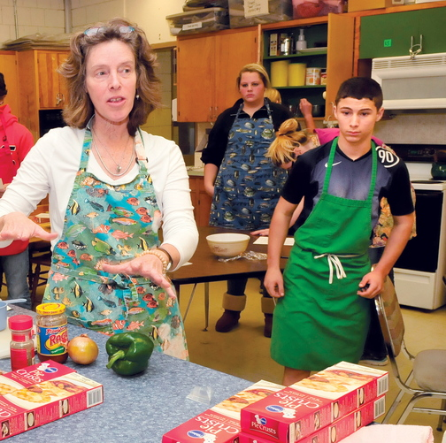 Skowhegan Area High School teacher Beth Scherpf speaks with students in the basic foods class last month. At right, student Jeremy Silva prepares to make pizza pockets.