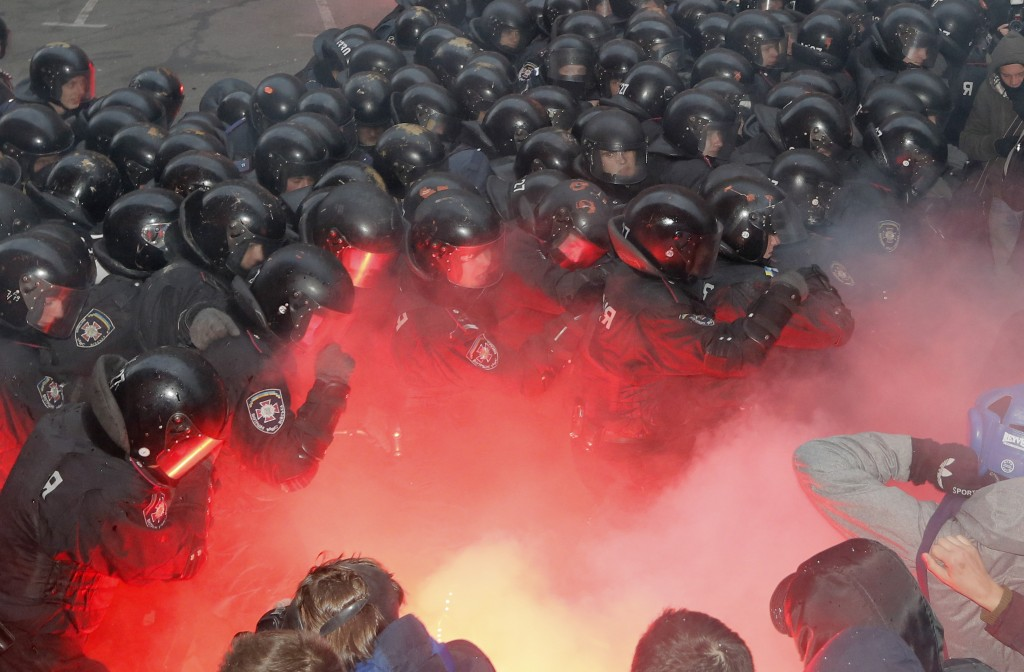 Protesters and police clash outside the presidential office in Kiev, Ukraine, on Sunday. Police drove them back with truncheons, tear gas and flash grenades.