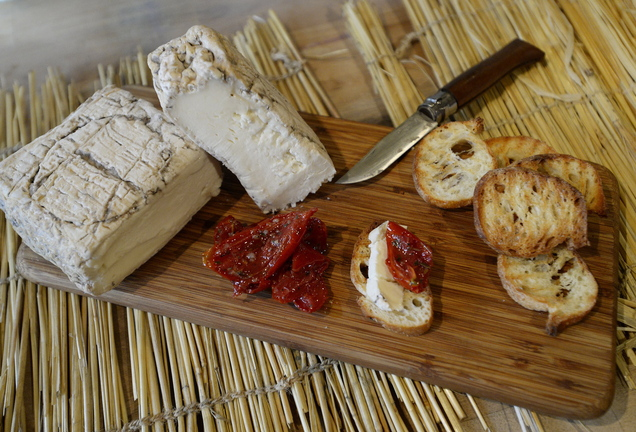 At The Cheese Iron in Scarborough, truffled cheeses, far left, and cave-aged taleggio from the Lombardy region of Italy are served with oven-roasted tomatoes.