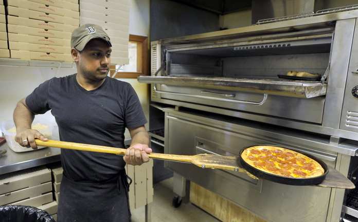 James Pyle of Falmouth slides a pizza from the oven at the Falmouth House of Pizza.