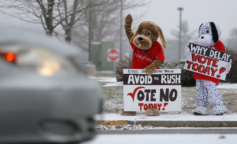 In this Nov. 25, 2013 file photo, Katy Foley and Ellen O'Keefe of Scarborough dress up as dogs outside the Town & Country Credit Union in Scarborough to encourage voters to reject a dog-leash law. Although voters decided Tuesday to repeal an ordinance banning unleashed dogs from all town property, the matter is far from over.