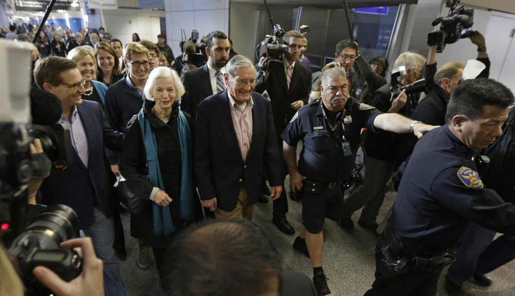 Merrill Newman, center, walks beside his wife, Lee, and his son Jeffrey, left, after arriving at San Francisco International Airport on Saturday. Newman was detained in North Korea late October at the end of a 10-day trip to North Korea, a visit that came six decades after he oversaw a group of South Korean wartime guerrillas during the 1950-53 war.