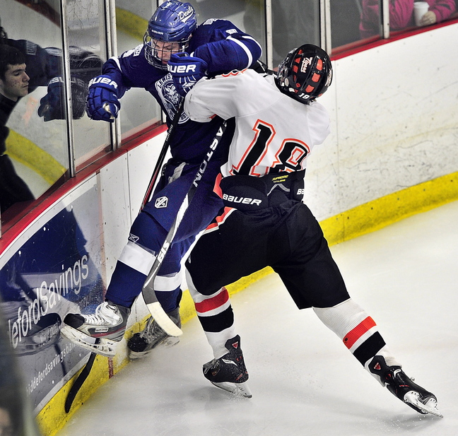 Max Bolduc of Lewiston gets checked into the boards by Biddeford's Corey Brown during their boys' hockey season opener Saturday afternoon at Biddeford Ice Arena. Lewiston won, 5-3.