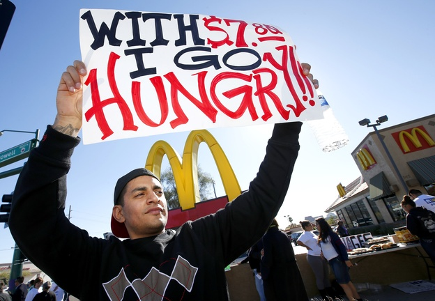 Alex Robles joins dozens of protesters at a rally against low wages for fast-food workers, in front of a McDonald's in Phoenix last Thursday. Opponents invariably predict that raising the minimum wage will discourage employers from hiring, but recent research has found otherwise. Arizona's minimum wage is $7.80 an hour; the minimum wage in Maine is $7.50.