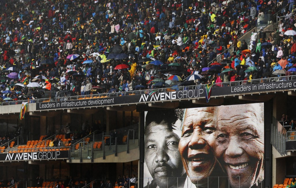 Faces of Nelson Mandela through the ages are shown on a big screen during the memorial service for former South African president Nelson Mandela at the FNB Stadium in Soweto, near Johannesburg, South Africa, Tuesday.