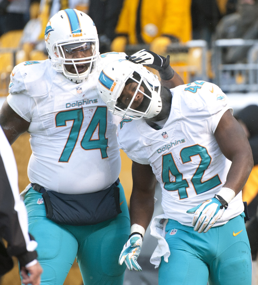 Miami Dolphins tight end Charles Clay, right, has been making a name for himself in recent weeks by eluding defenders like Pittsburgh's Troy Polamalu.