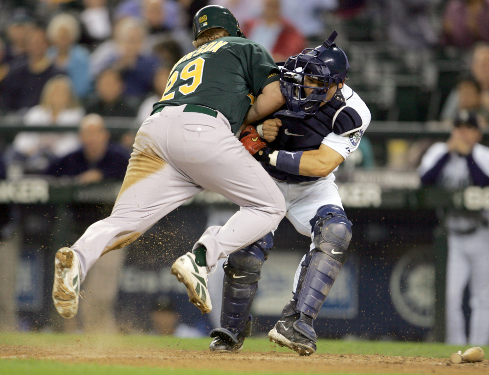 In this Sept. 27, 2006, file photo, Oakland Athletics' Dan Johnson, left, collides with Seattle Mariners' Kenji Johjima at home plate but was out on the play as Johjima held onto the ball in the ninth inning of a baseball game at Safeco Field in Seattle. New York Mets general manager Sandy Alderson, chairman of the rules committee, announced Wednesday, Dec. 11, 2013, that Major League Baseball plans to eliminate home plate collisions. He said player health and increased awareness of concussions were behind the decision.