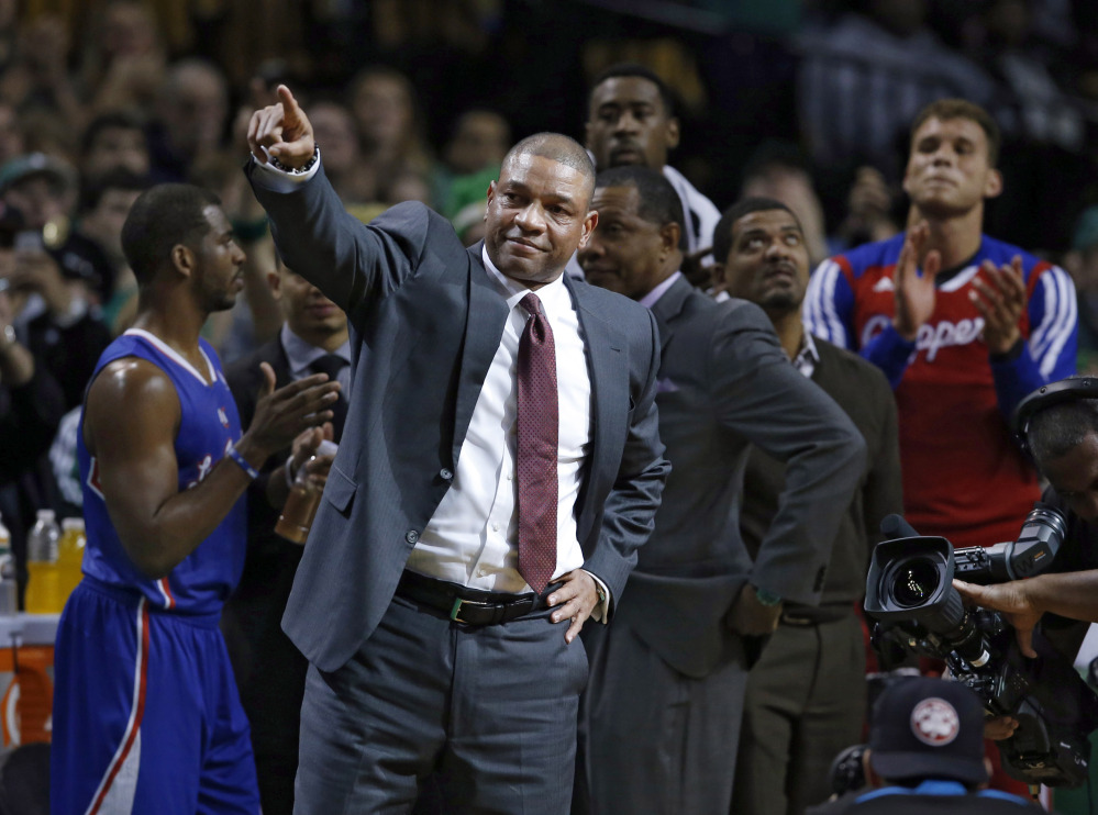 Doc Rivers, the former Celtics coach who is now head coach for the Los Angeles Clippers, points to acknowledge fans during a video tribute to him in his first time back on the sidelines at the TD Garden on Wednesday night.