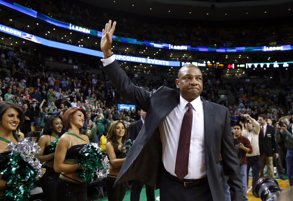 Doc Rivers, former head coach of the Boston Celtics and current head coach of the Los Angeles Clippers, waves to cheering fans as he enters the TD Garden floor for his first time back, before an NBA basketball game in Boston on Wednesday.