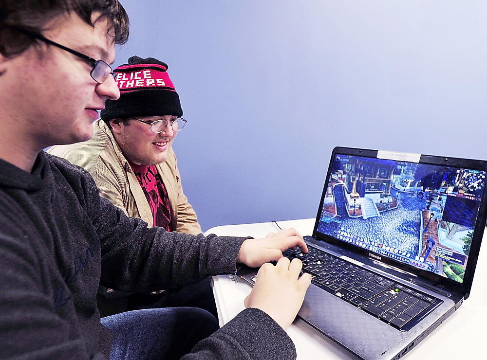 """Victor Smith of Portland, left, plays his customized character with dozens of others online Thursday in """"World of Warcraft."""" Helping Smith with strategyis his friend, Keegan Beal."""