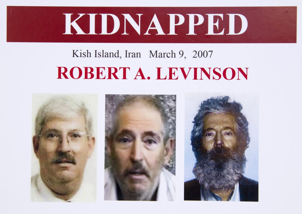 An FBI poster showing a composite image of retired FBI agent Robert Levinson, right, of how he would look like now after five years in captivity, and an image, center, taken from the video, released by his kidnappers, and a picture before he was kidnapped, left, displayed during a news conference in Washington, on March 6, 2012.