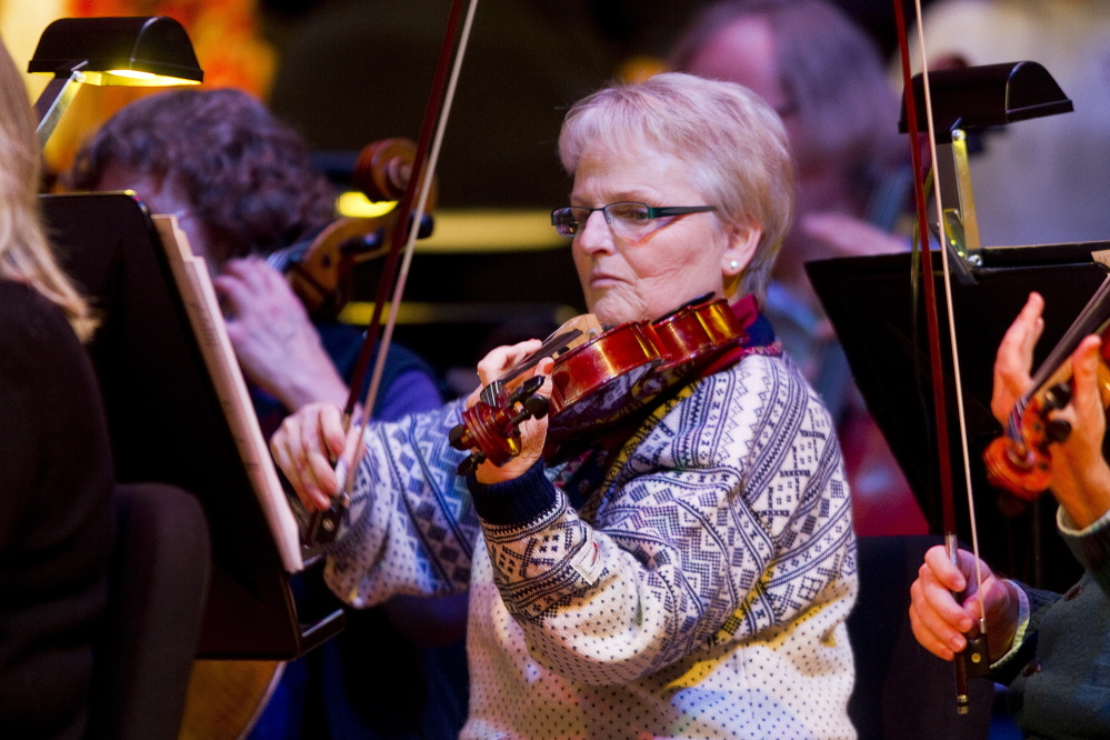"""Carl D. Walsh/Staff Photographer Portland Symphony Orchestra violist Ann Stepp plays during the final """"Magic of Christmas"""" at Merrill Auditorium in Portland on Thursday. Her daughter surprised her before the rehearsal by telling her she was also performing in the show."""