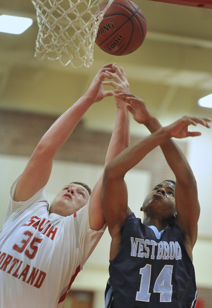 Jaren Muller, left, who scored 33 points and pulled down 14 rebounds for South Portland, battles with Westbrook's Demetrius Hoskins during Friday's game in South Portland