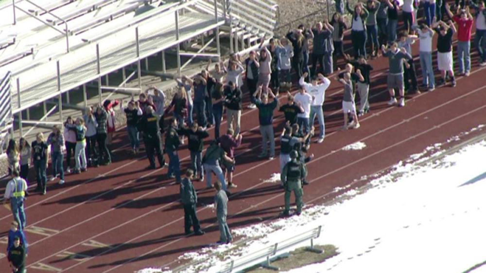 In this image taken from video provided by Fox 31 Denver, students gather just outside of Arapahoe High School as police respond to reports of a shooting Friday.