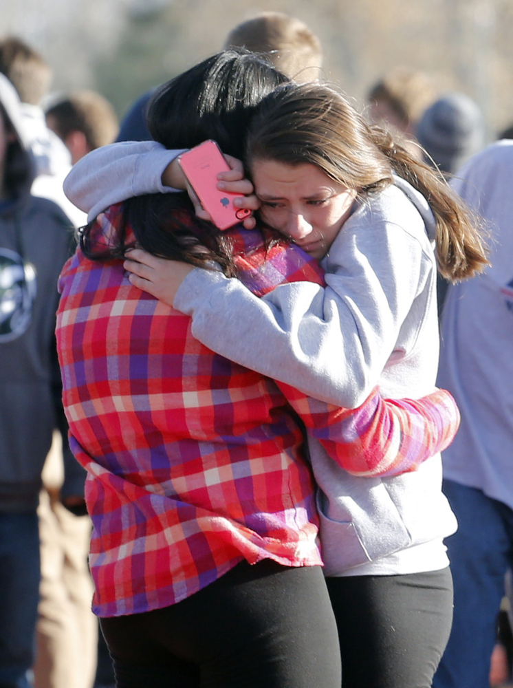 Students comfort each other outside of Arapahoe High School after a shooting on the campus in Centennial, Colo., on Friday. Arapahoe County Sheriff Grayson Robinson said the shooter wounded two students before killing himself.