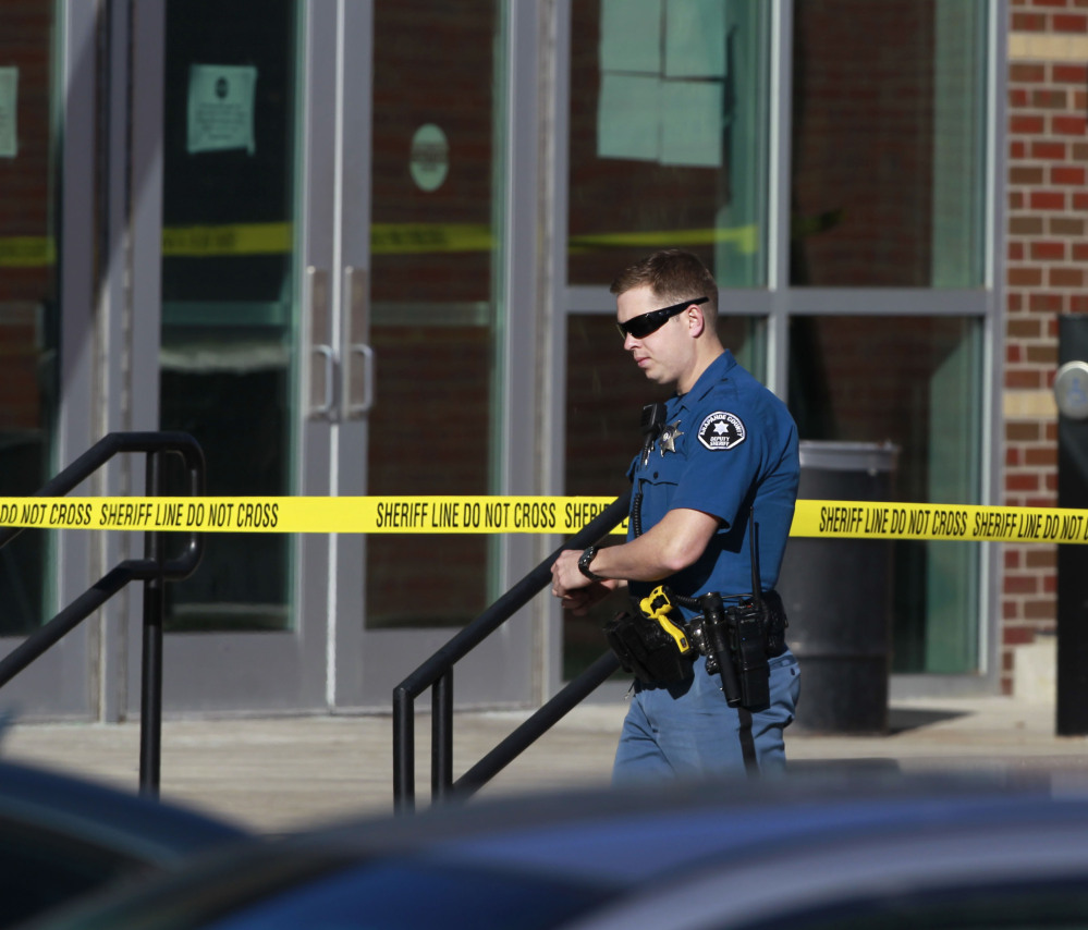 A deputy of the Arapahoe County (Colo.) Sheriff's Department walks past crime scene tape Saturday at Arapahoe High School in Centennial, Colo. The student who killed himself was angry with the debate coach.