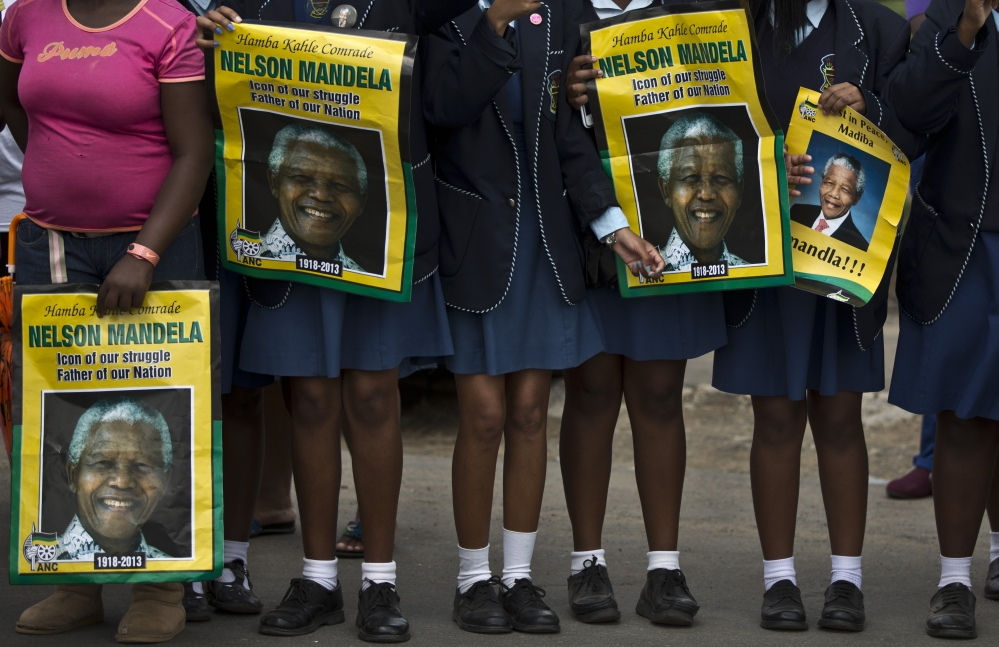 South African schoolgirls hold posters of Nelson Mandela as they wait for the former president's casket Saturday.