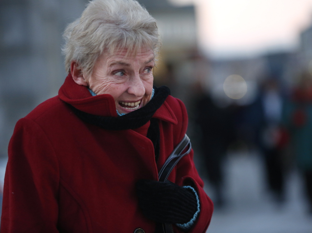 Patricia Gorham of Saco reacts to the cold air Friday as she waits for her ride to pick her up outside the Merrill Auditorium. A winter storm was expected late Saturday followed by more cold temperatures.