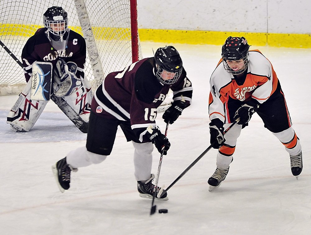 Megan Demers, center, of Gorham/Bonny Eagle battles for the puck with Biddeford's Katherine Dumoulin as Gorham/Bonny Eagle goalie Maddy Hamblen looks on Saturday at Biddeford Ice Arena. Dumoulin scored her second goal of the game 17 seconds into overtime to give Biddeford a 3-2 win.